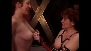Mature mistress in a leather suit hangs clothespins on her young slave's shaved pussy